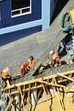 I costruttori versano il cemento ad un muro di cemento Immagini Stock