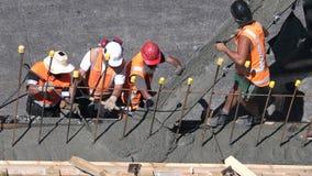 I costruttori versano il cemento ad un muro di cemento archivi video