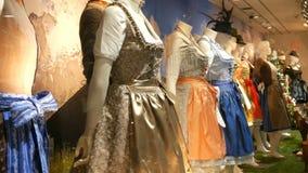 I costumi bavaresi nazionali dirndl delle belle varie donne ed i lederhosen degli uomini sulla finestra del negozio stock footage
