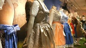 I costumi bavaresi nazionali dirndl delle belle varie donne ed i lederhosen degli uomini sulla finestra del negozio archivi video