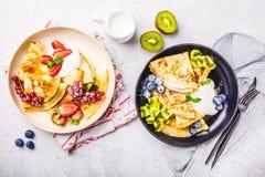 I crêpe sottili casalinghi sono servito con la crema della cagliata, i frutti ed i piatti delle bacche in bianco e nero, vista su immagini stock