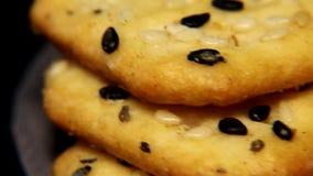 I cracker croccanti gialli luminosi su un substrato di tessuto sintetico grezzo girano sulla tavola stock footage