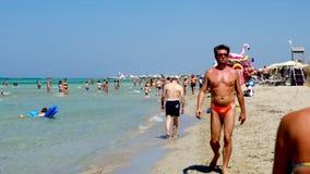 I creatori di festa di Salento camminano mare ionico delle acque cristalline della spiaggia di Torre San Giovanni della riva video d archivio