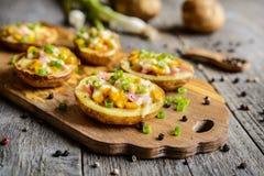 I crogioli di patata hanno riempito di mais, di prosciutto, di formaggio e di cipolla verde Fotografia Stock