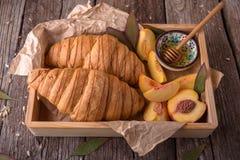 I croissant al forno con frutta si inceppano di recente, caramello e miele sui bordi di legno fotografie stock