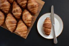 I croissant di recente al forno su fondo nero Stile piano fotografia stock