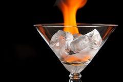 I cubetti di ghiaccio in vetro con la fiamma sul nero brillante sorgono Fotografia Stock
