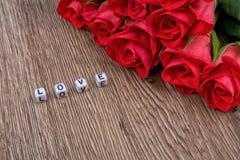I cubi come iscrizione amano su un fondo di legno Fotografia Stock