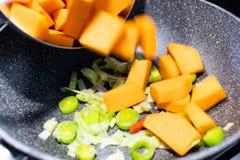 I cubi del porro e della zucca sono cucinati e sautéed in un PA antiaderante immagine stock