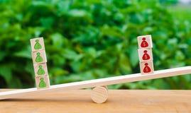 I cubi sulle scale con i modelli verdi di soldi superano il rosso in peso Il concetto di eccedenza, di crescita di profitto e di  immagini stock libere da diritti