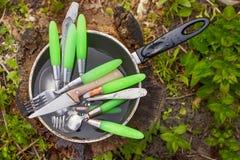 I cucchiai, le forchette ed i coltelli sporchi sono nella pentola su un legno af del ceppo Fotografia Stock Libera da Diritti