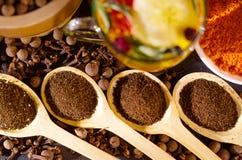 I cucchiai rustici di legno del primo piano hanno riempito con la polvere fresca della tisana, altri tè e le spezie nel fondo, mo Fotografia Stock