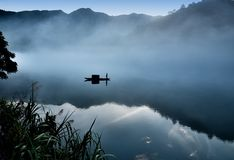 I cucoloris di un fishman sulla barca nella nebbia sul fiume, una chiara riflessione sul fiume calmo Tono freddo fotografia stock