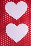 I cuori bianchi hanno scolpito da carta su un fondo rosso ` S del biglietto di S. Valentino Fotografia Stock