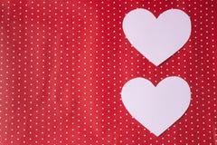 I cuori bianchi hanno scolpito da carta su un fondo rosso ` S del biglietto di S. Valentino Immagini Stock