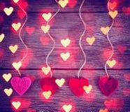 I cuori del biglietto di S. Valentino del tessuto del feltro che appendono sul legname galleggiante rustico Fotografia Stock Libera da Diritti