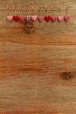 I cuori del biglietto di S. Valentino di amore del percalle che appendono sul backgr di legno di struttura Fotografie Stock