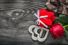 I cuori della rosa rossa hanno imballato la scatola attuale sulle celebrazioni del bordo di legno Immagine Stock Libera da Diritti