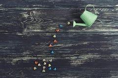 I cuori multicolori versano fuori dall'annaffiatoio su un fondo di legno scuro Giorno del `s del biglietto di S fotografia stock