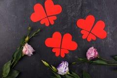 I cuori sono allineati in primo piano delle farfalle e da sotto le rose giapponesi su un fondo di pietra Vista da sopra Immagine Stock