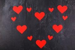 I cuori sono allineati in un grande cuore su un fondo di pietra Fotografia Stock