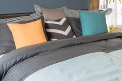 i cuscini variopinti su colore scuro inseriscono in camera da letto moderna fotografia stock libera da diritti