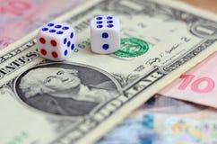 I dadi bianchi sono su una banconota in dollari dei dollari americani Il concetto di gioco con i tassi nell'unità monetaria Fotografie Stock