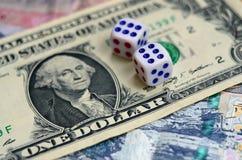 I dadi bianchi sono su una banconota in dollari dei dollari americani Il concetto di gioco con i tassi nell'unità monetaria Immagini Stock