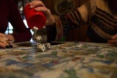 I dadi di rotolamento fuori foggiano a coppa il gioco del gioco della famiglia Fotografia Stock Libera da Diritti
