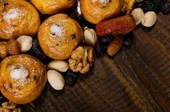 I dadi, i frutti secchi, i pistacchi ed i biscotti casalinghi hanno sparso dalla borsa sulla tavola con un posto per scrivere immagine stock