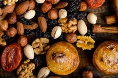 I dadi, i frutti secchi, i pistacchi ed i biscotti casalinghi sono sparsi dalla borsa sulla tavola fotografia stock