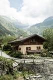 By i dalen av schweiziska fjällängar Arkivbilder