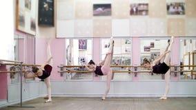 I danskorridor är unga ballerina i svarta body sträckning som står den near barren på spegeln i balettgrupp arkivfilmer