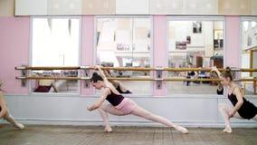 I danskorridor sträcker unga ballerina i svarta body parterren som står den near barren på spegeln i balett arkivfilmer