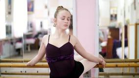 I danskorridor ung ballerina i den svarta bodyen som tillbaka sträcker på barren, står elegantly som den near barren på spegeln lager videofilmer