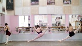 I danskorridor unga ballerina i svarta body som sträcker på barren, på pointeskor, står elegantly som den near barren arkivfilmer