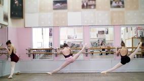 I danskorridor unga ballerina i svarta body som sträcker på barren, på pointeskor, står elegantly som den near barren stock video