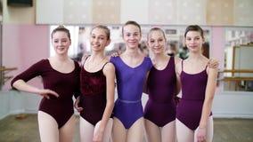 I danskorridor unga flickor som ballerina i purpurfärgade body kramar, ler, underbara balettskolastudenter, lager videofilmer