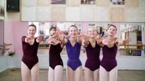 I danskorridor unga flickor som ballerina i purpurfärgade body kramar, ler, underbara balettskolastudenter som blåser kyssar stock video