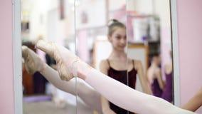 I danskorridor utför den unga ballerina i purpurfärgad body developpe åt sidan på pointeskor, lyfter upp hennes ben elegantly lager videofilmer