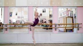 I danskorridor utför den unga ballerina i purpurfärgad body developpeinställning på pointeskor, lyfter upp hennes ben bakom lager videofilmer