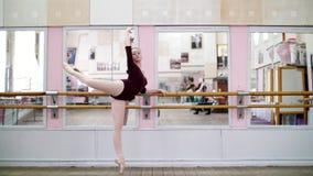 I danskorridor utför den unga ballerina i purpurfärgad body developpeinställning på pointeskor, lyfter upp hennes ben bakom arkivfilmer