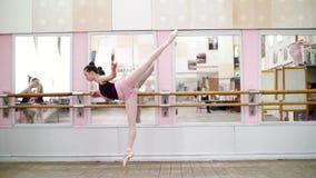I danskorridor utför den unga ballerina i purpurfärgad body elegantly en bestämd balettövning, arabesque i lutning stock video