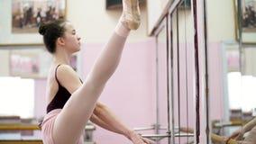 I danskorridor utför den unga ballerina i purpurfärgad body elegantly en bestämd balettövning, developpe en la i andra hand stock video