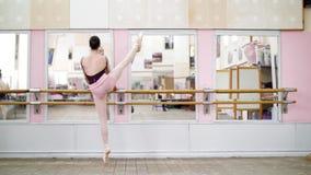 I danskorridor utför den unga ballerina i purpurfärgad body elegantly en bestämd balettövning, developpe en la i andra hand arkivfilmer