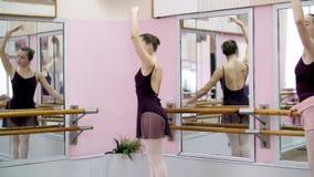 I danskorridor utför den unga ballerina i purpurfärgad body elegantly en bestämd balettövning, storslagen battementbaksida lager videofilmer