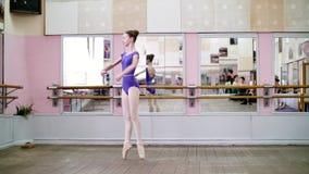 I danskorridor utför den unga ballerina i purpurfärgad body turnerar chenne på pointeskor, flyttningar med vänd elegantly, på stock video