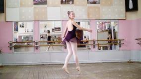 I danskorridor utför den unga ballerina i purpurfärgad body turnerar jete en-dedans, henne flyttar sig till och med balettgruppen arkivfilmer