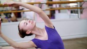 I danskorridor utför den unga ballerina i purpurfärgade body den delde behå I 3 positionen med framåt lutande, flicka är stock video