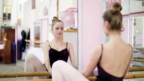 I danskorridor utför den unga ballerina i svart body en bestämd balettövning på barren, elegantly som, nära står lager videofilmer